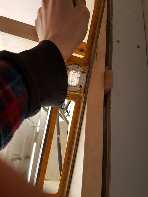 Fitting a combination frame using some packers and a spirit level